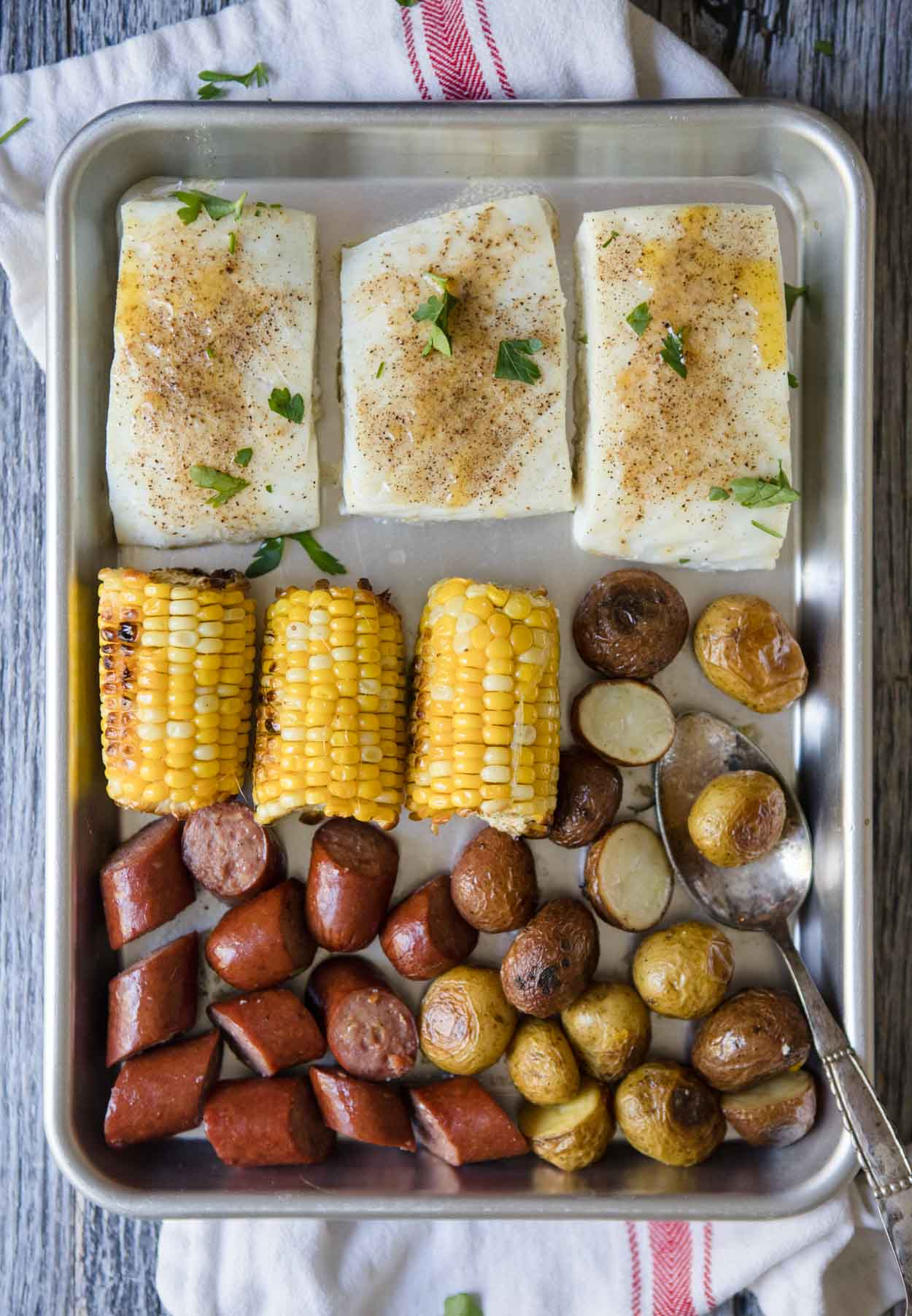 halibut, corn, sausage, and potatoes on a silver baking tray