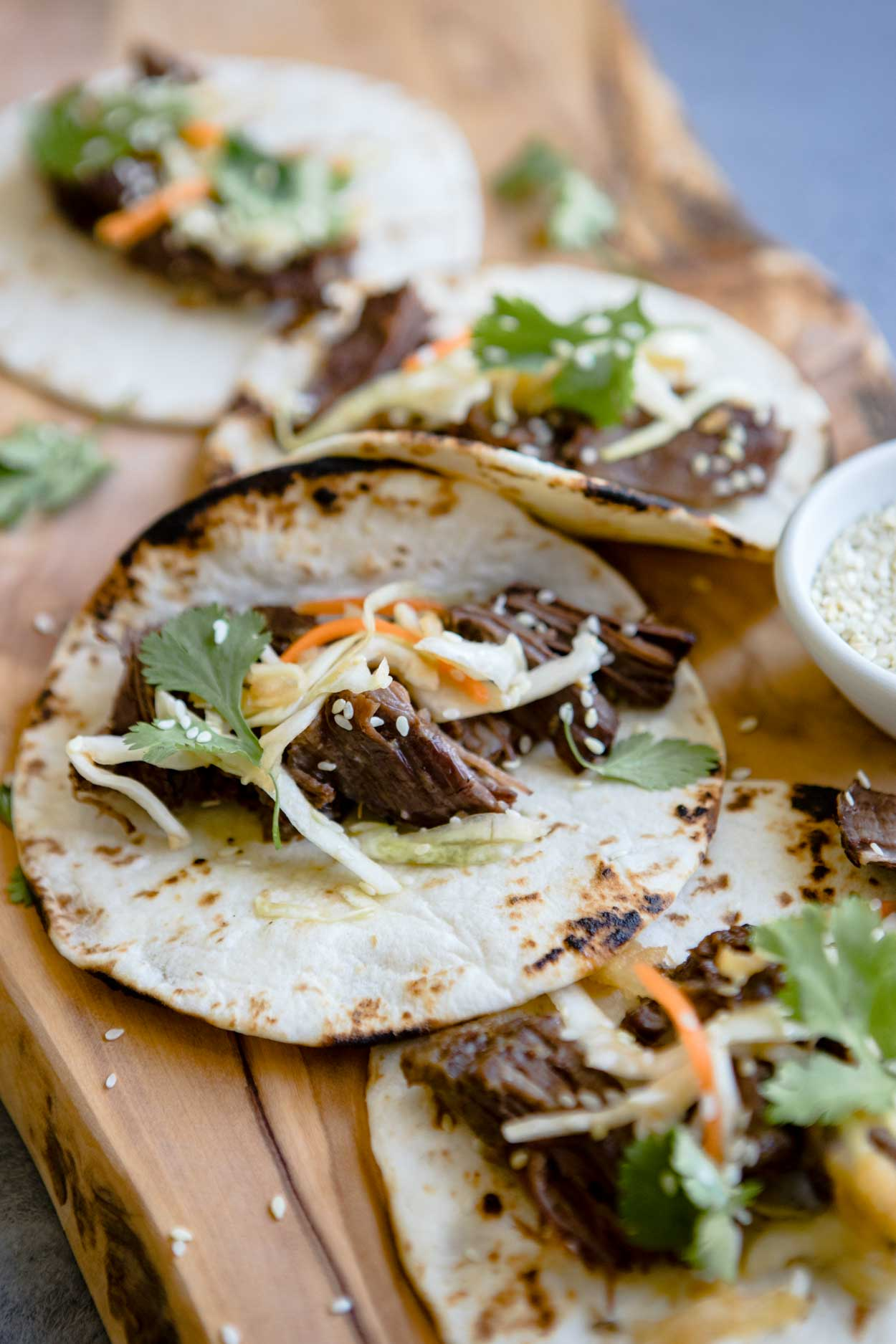 close up shot of beef tacos with shredded cabbage on top, on a wooden board