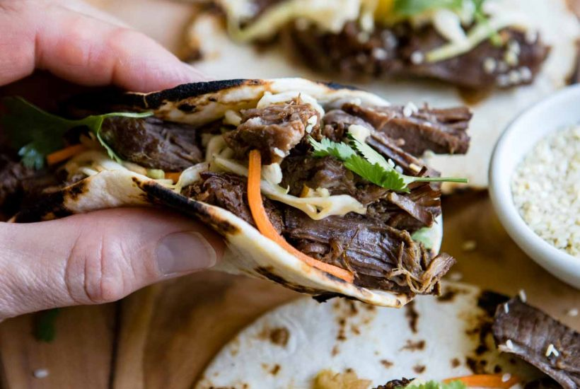 close up picture of a man holding a korean beef taco over a wooden board