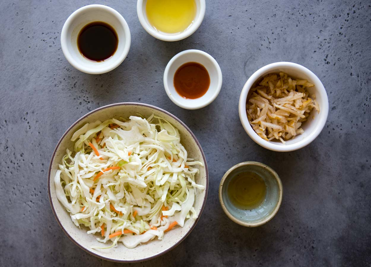 Coleslaw ingredients in round bowls on a gray background