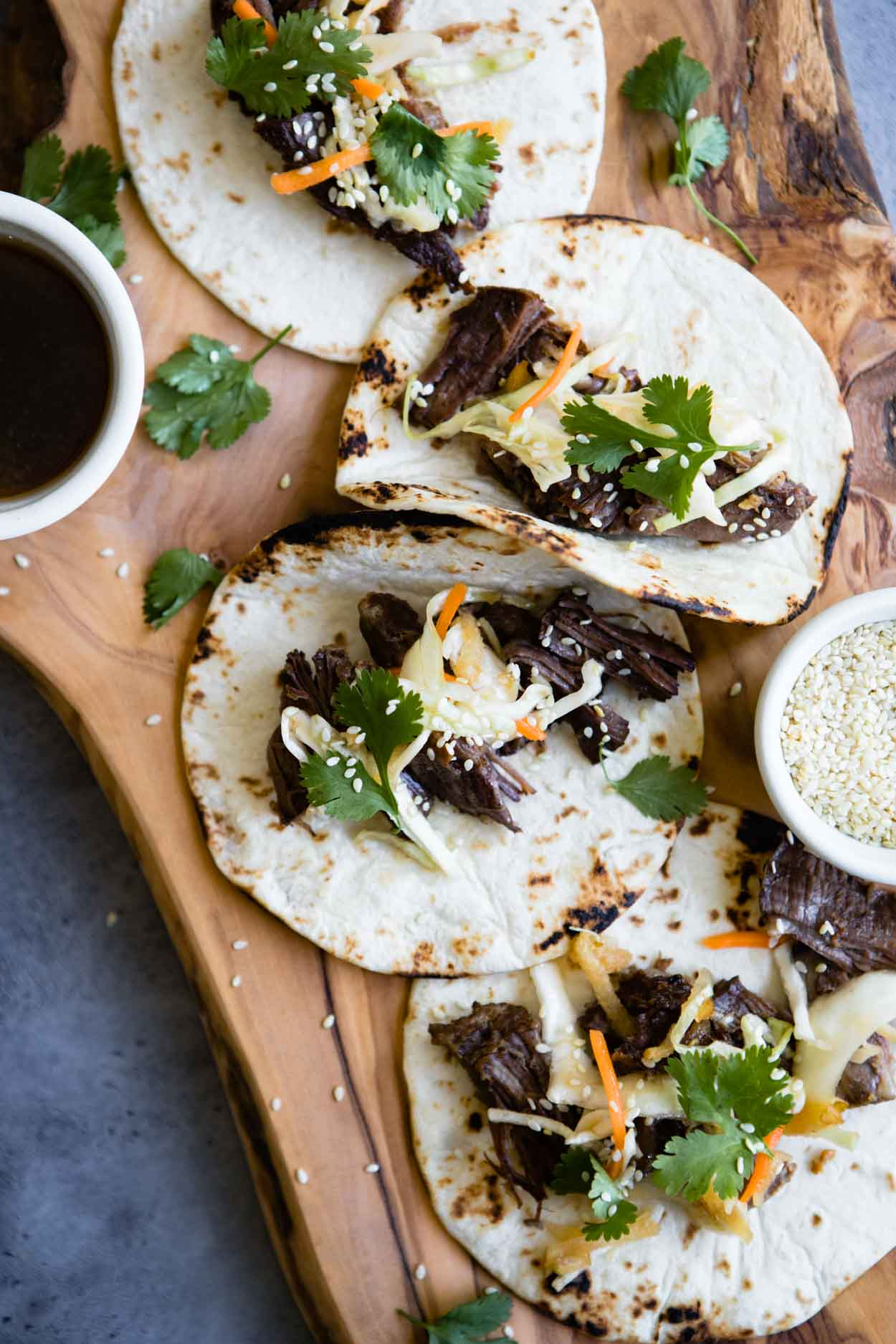 beef tacos with korean coleslaw topped on flour tortillas on a wooden board