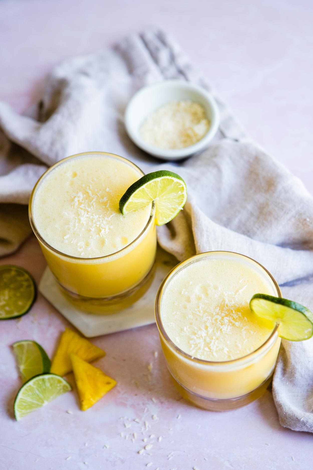overhead shot of 2 glasses of coconut pineapple margarita with lime wedges and pineapple garnish