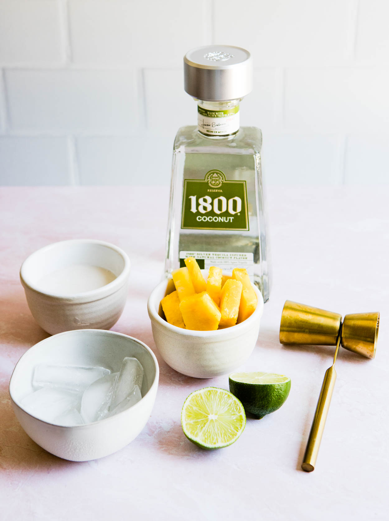 1800 coconut tequila with pineapple and ice and coconut milk in white bowls