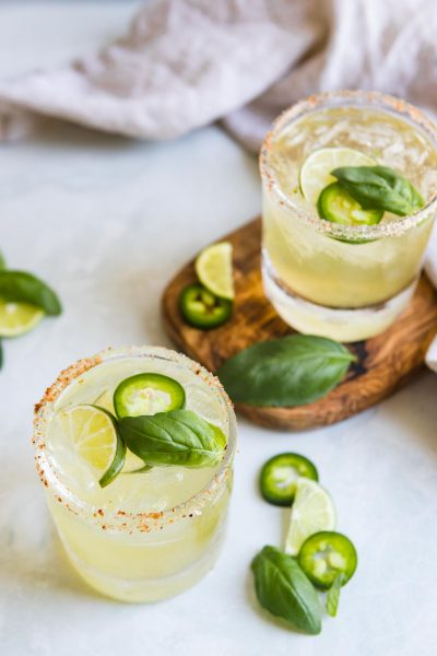 glasses filled with jalapeno margaritas garnished with basil, cucumber and jalapeno