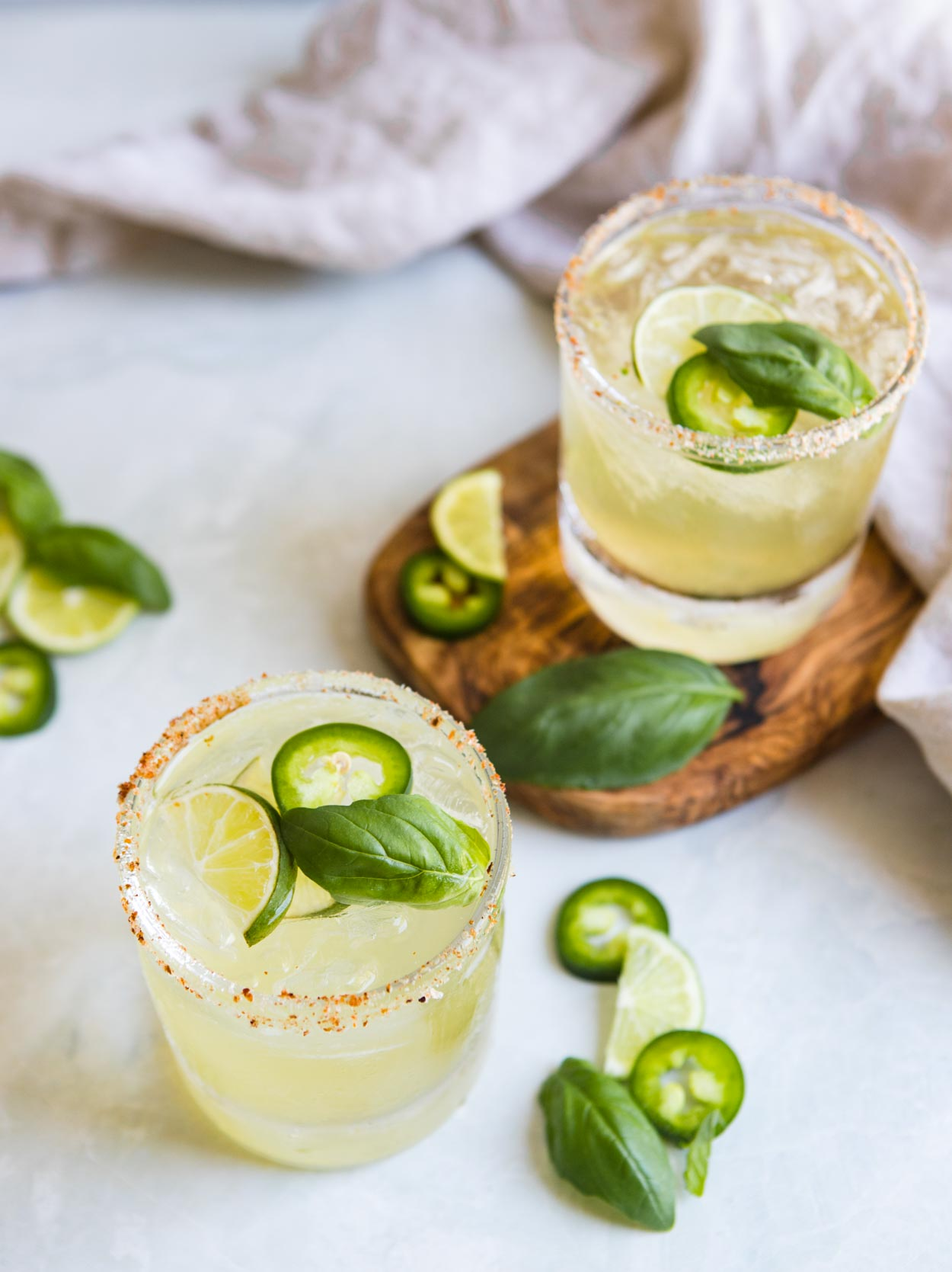 2 glasses filled with cucumber basil jalapeno margarita against a white background