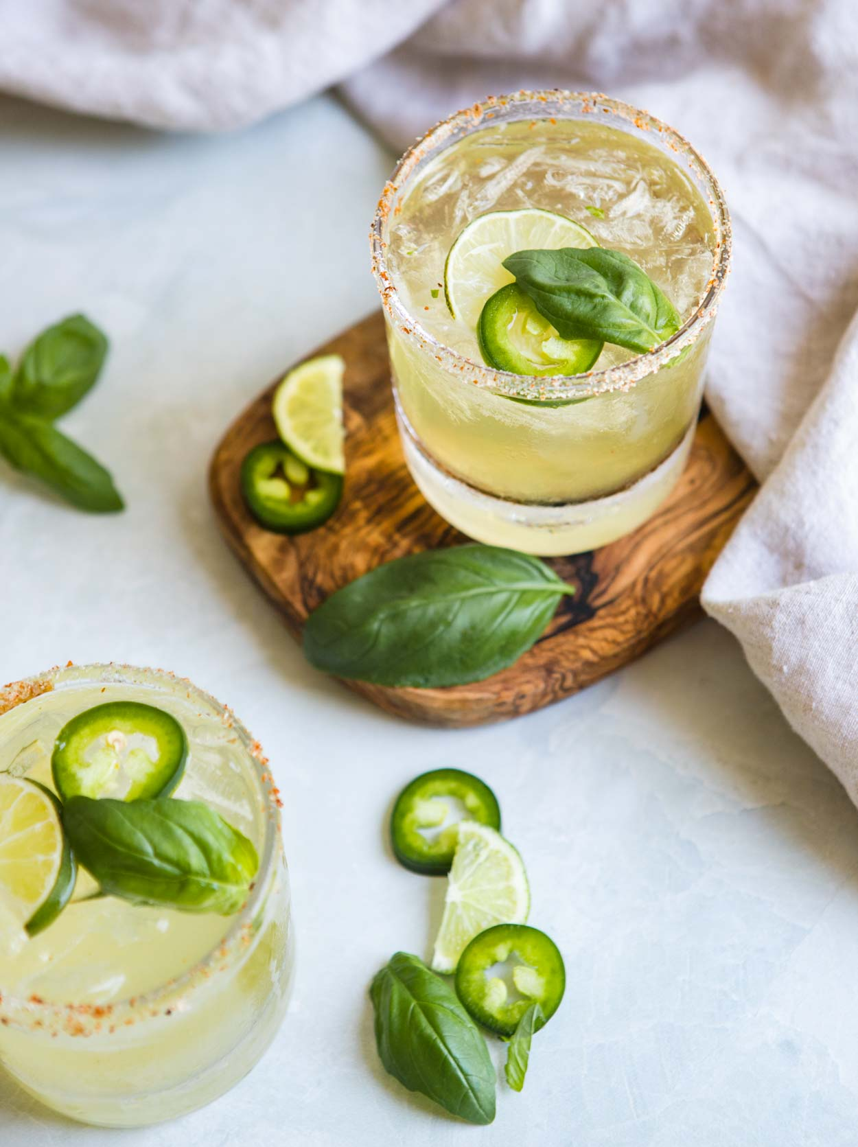 close up glass of jalapeno margarita recipe with lime, cucumber and basil garnish