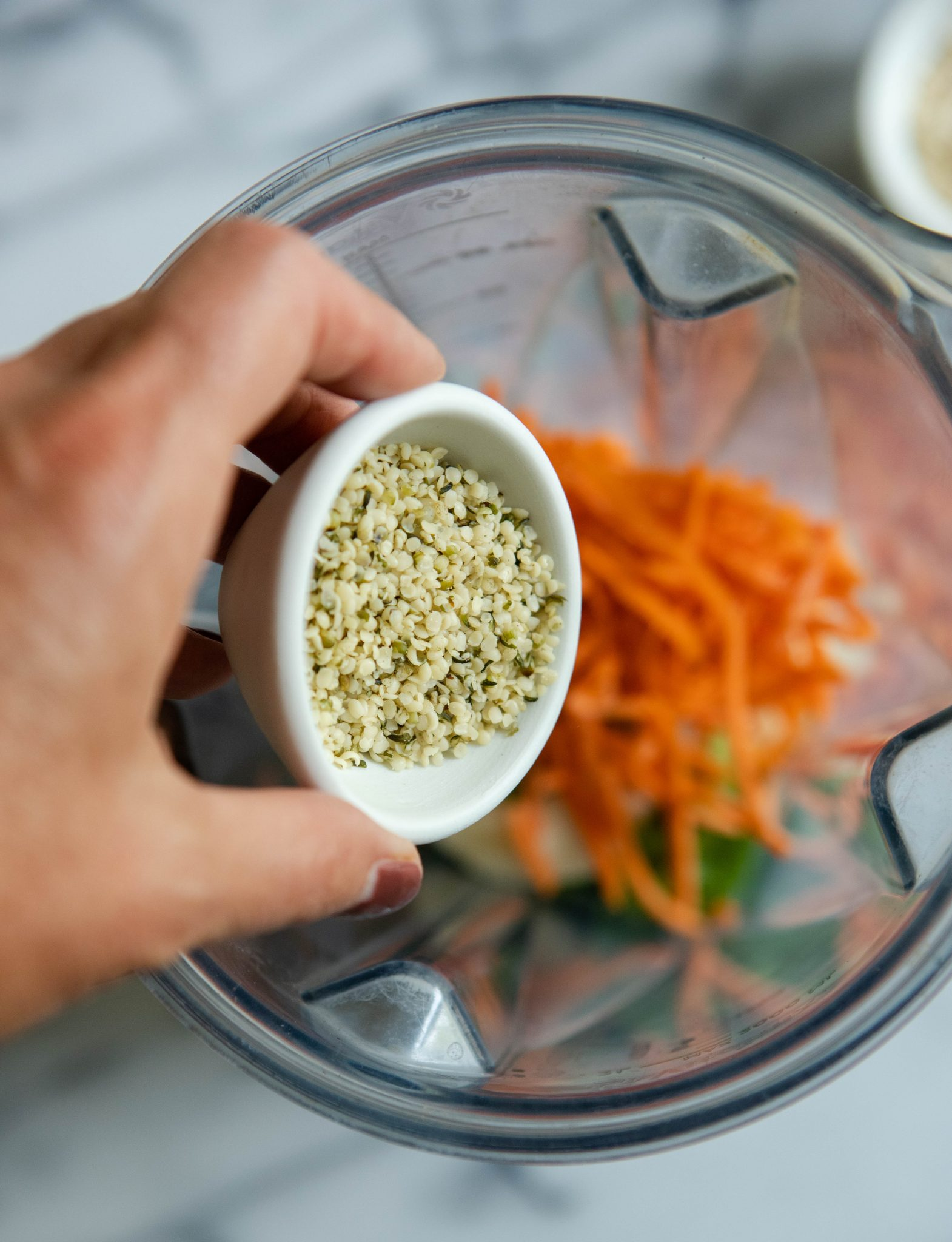 hemp seeds being poured into a blender