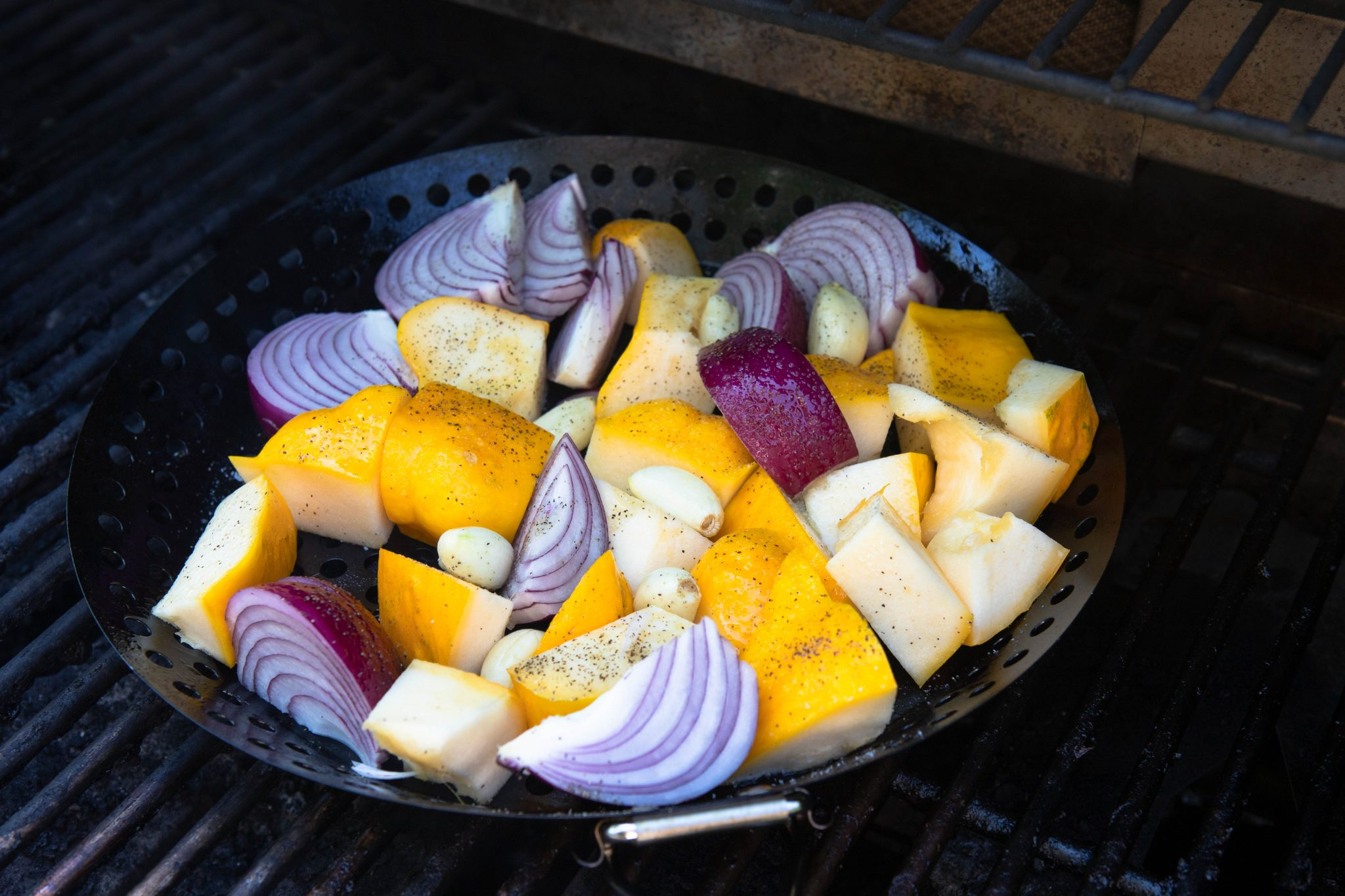 grilled vegetables in a grill basket on a bbq