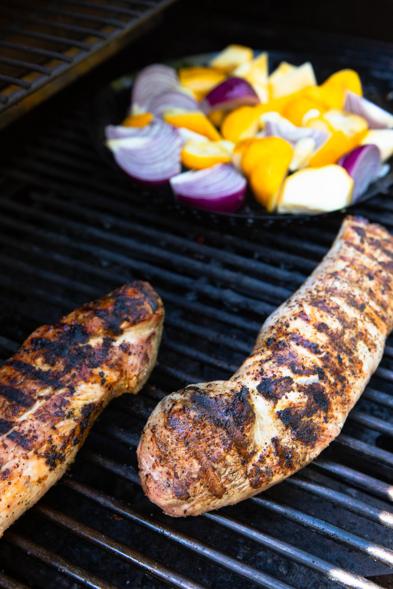 2 pieces of pork tenderloin and summer vegetables on a bbq grill