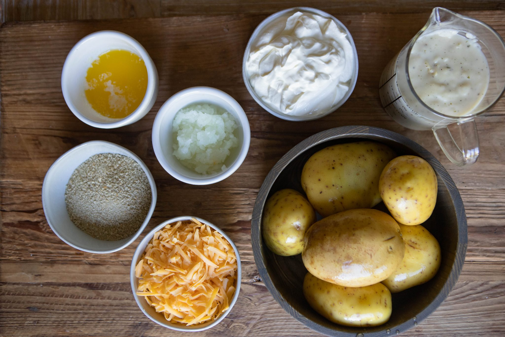 potatoes and other ingredients on a wooden board, for a casserole recipe