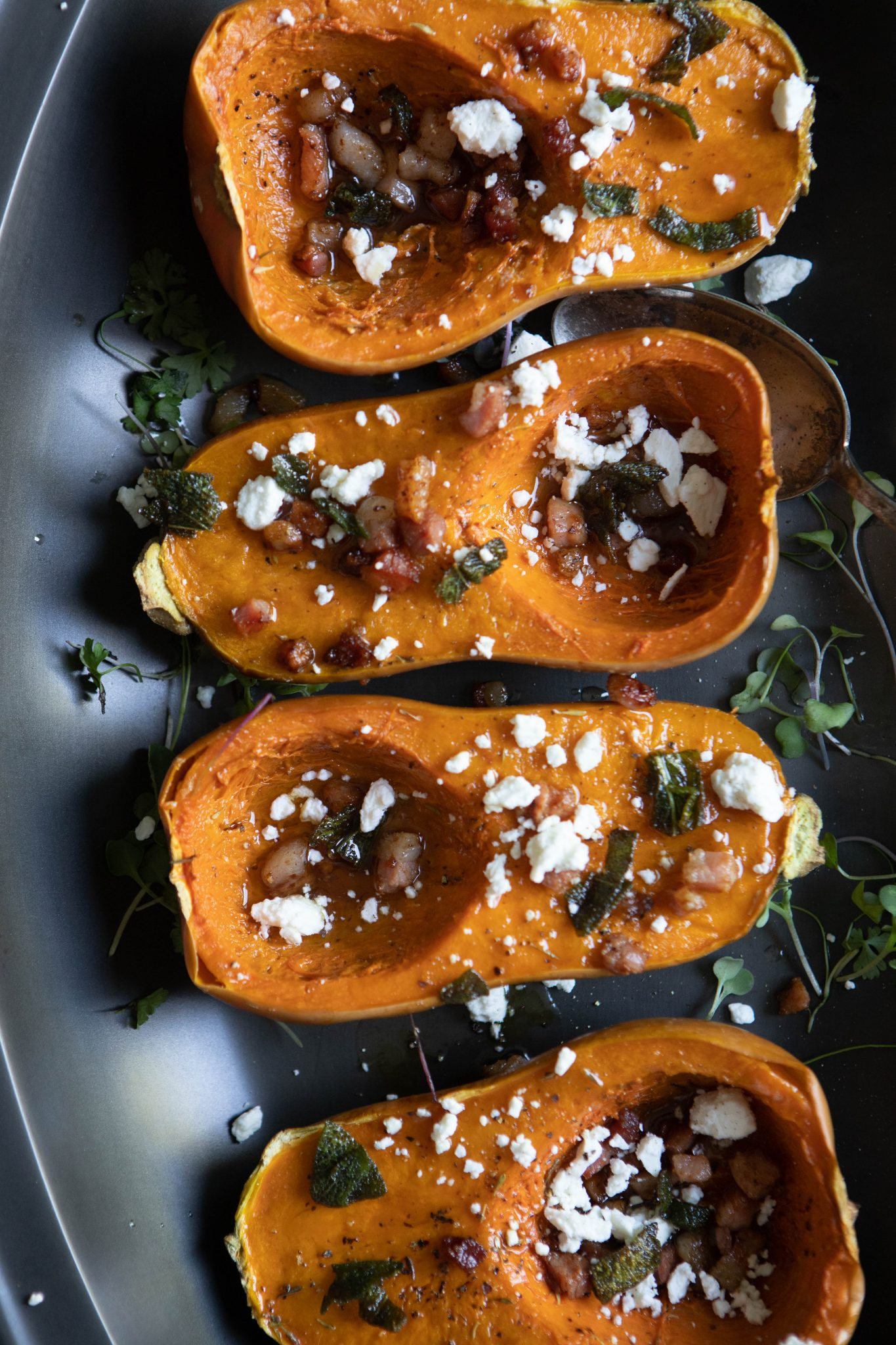 black platter with 4 roasted butternut squashes sprinkled with goat cheese and pancetta