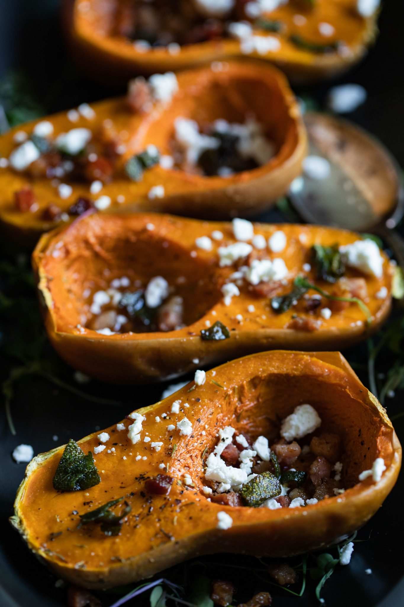 mini squash with pancetta and goat cheese sprinkled on top, assembled on a black platter