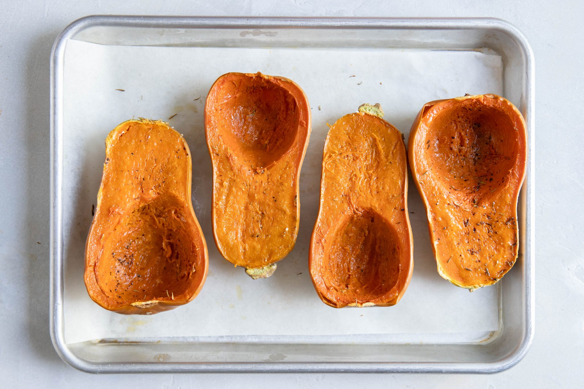 baked honeynut squash on a baking sheet with parchment paper