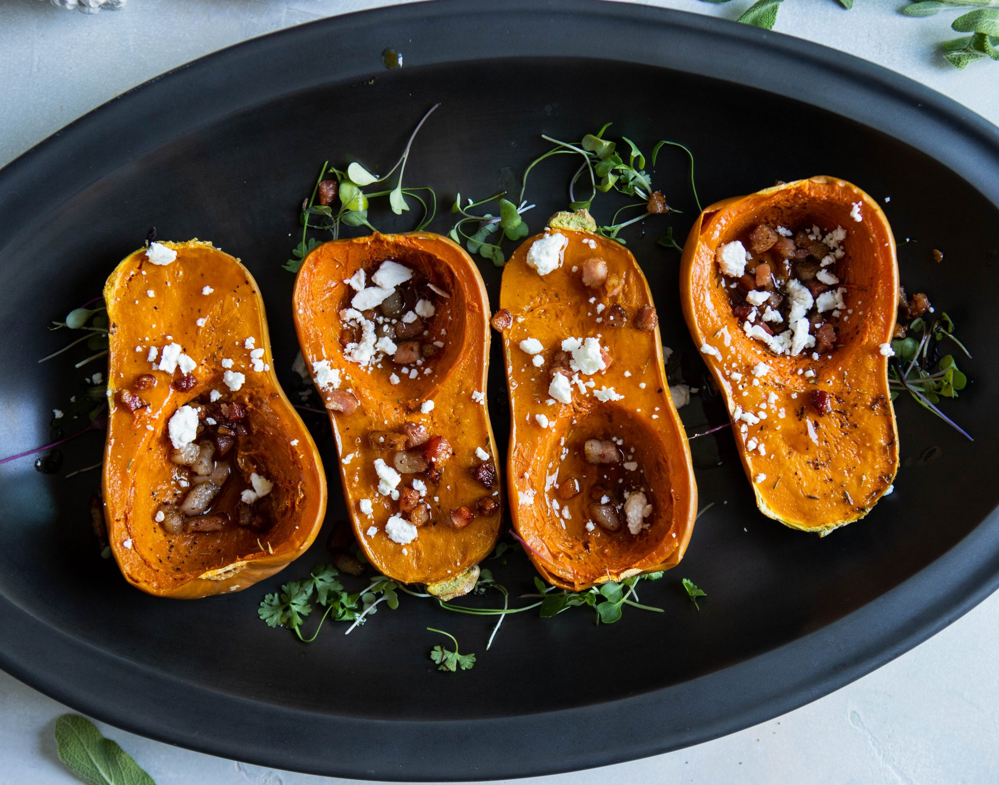 baked squash with pancetta and goat cheese sprinkled on top, in a black serving platter
