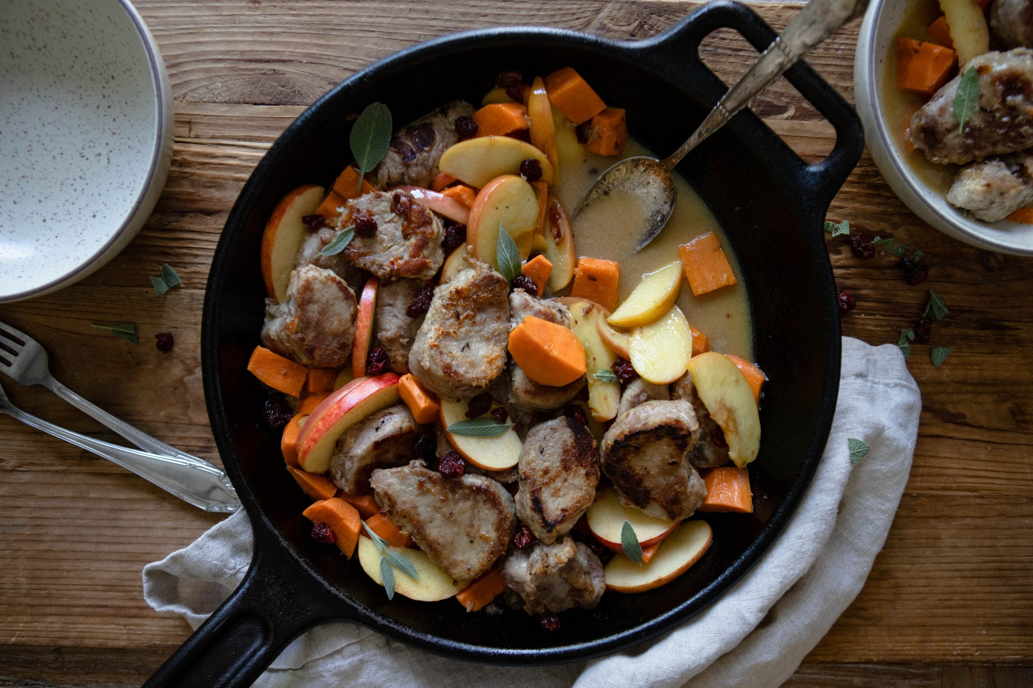 black cast iron skillet with pork tenderloin, apples and sweet potatoes on a wooden board