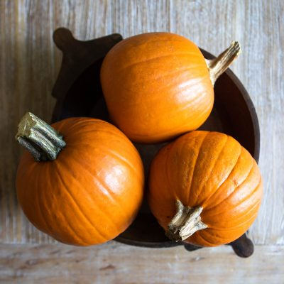 3 orange pumpkin pie pumpkins in a wooden bowl