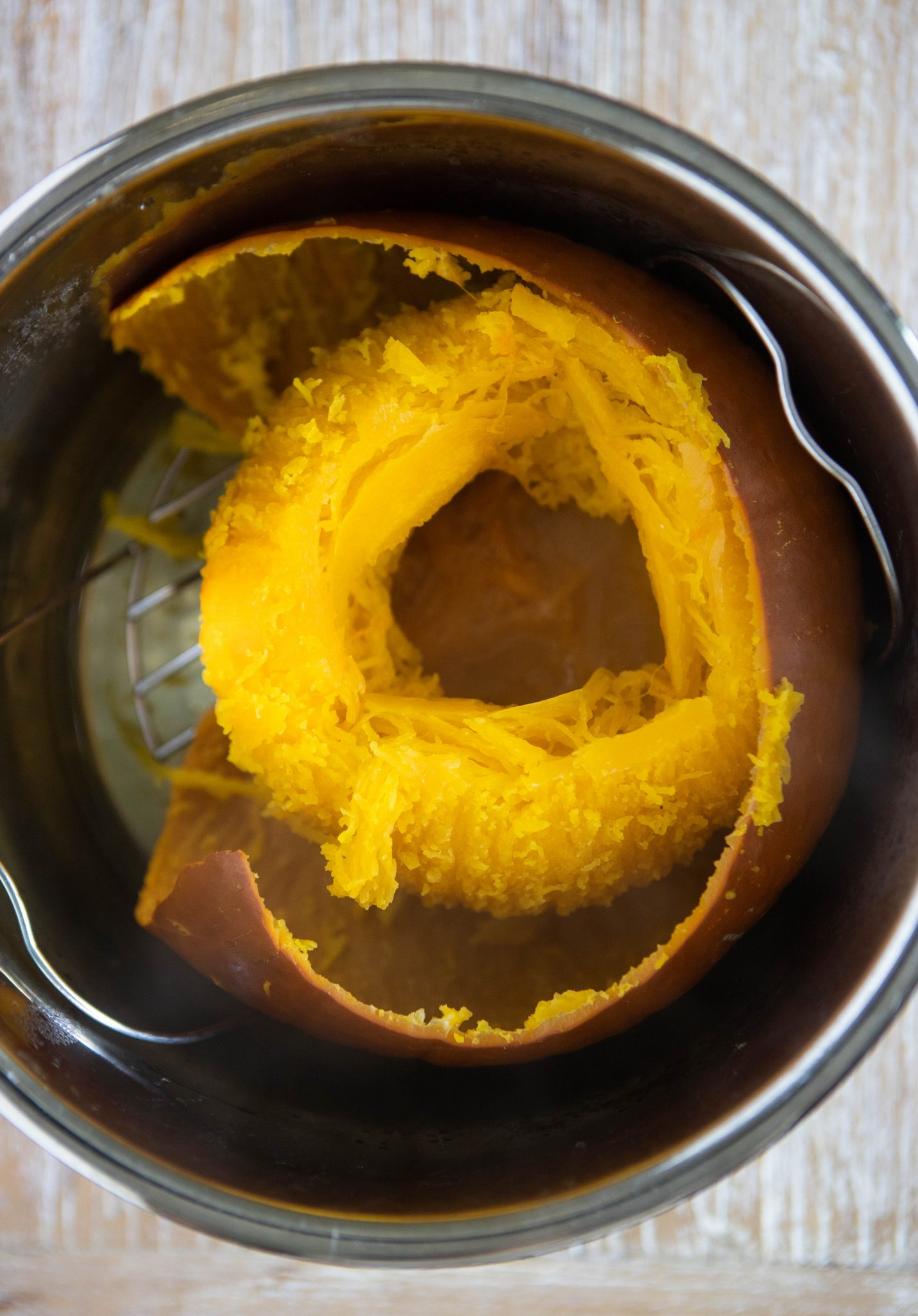 pumpkin cut open and cooked in the insert of an Instant Pot