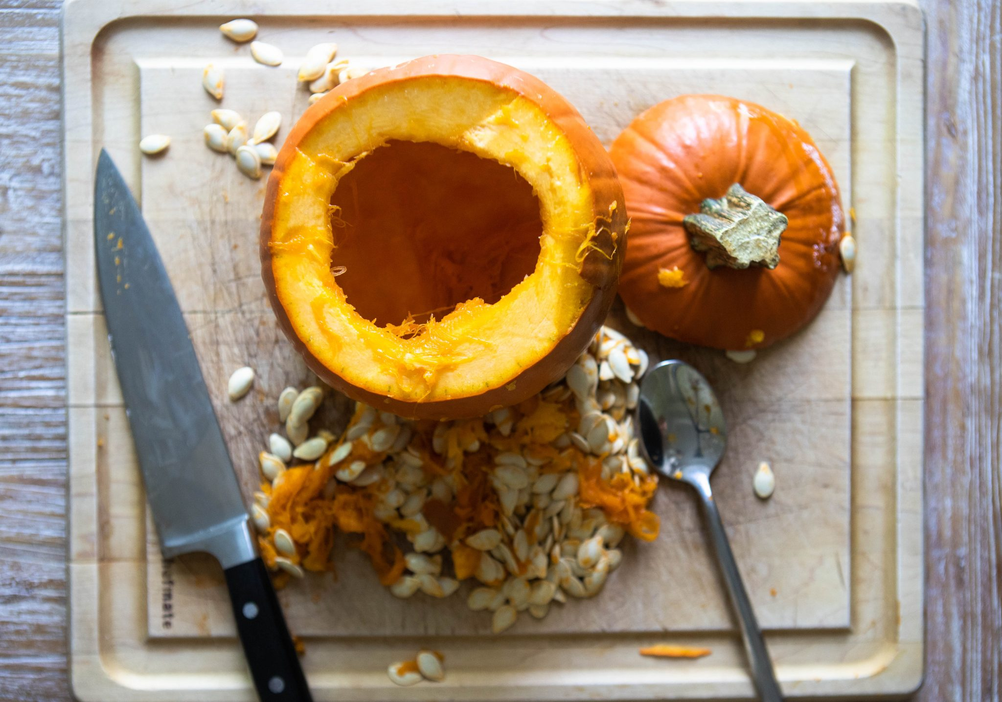 cutting board with a pumpkin cut open and seeds scooped out, next to a knife