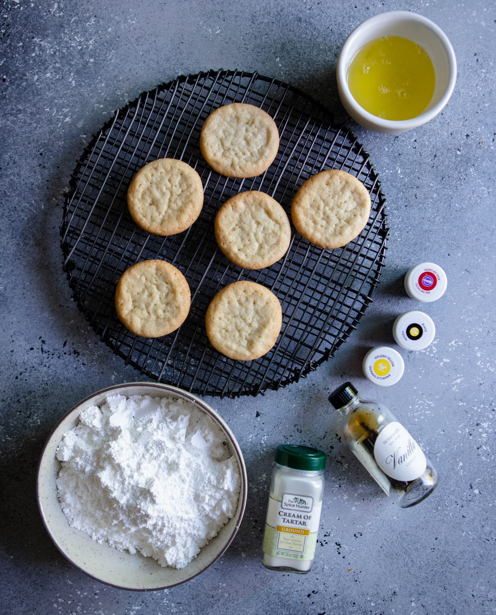 sugar cookies on a black cooling rack with the ingredients to make royal icing spread out on a gray board