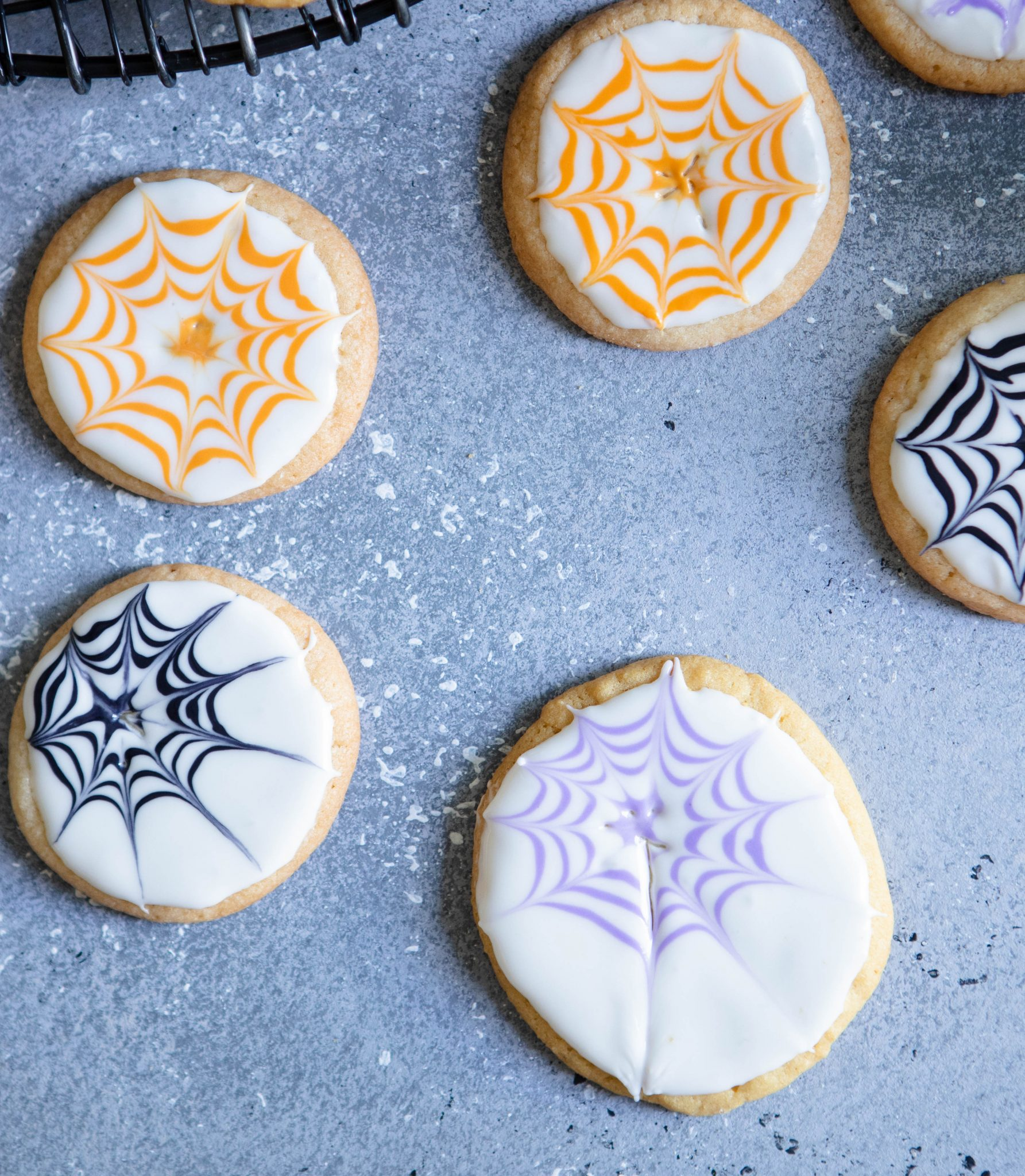 close up details of royal icing sugar cookies being decorated with a spider web for Halloween