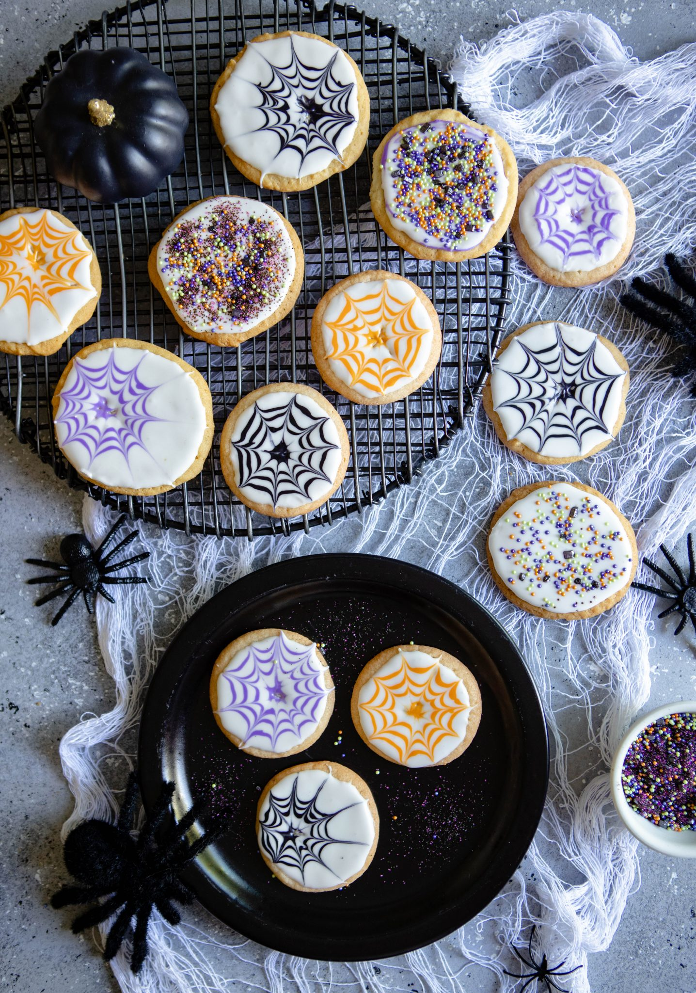 a black tray with Halloween spider web cookies decorated on top