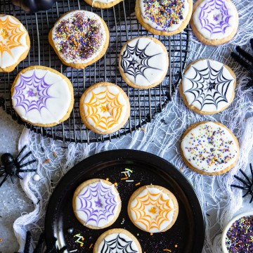 A spread of Halloween cookies decorated with Royal Icing and Spider Webs