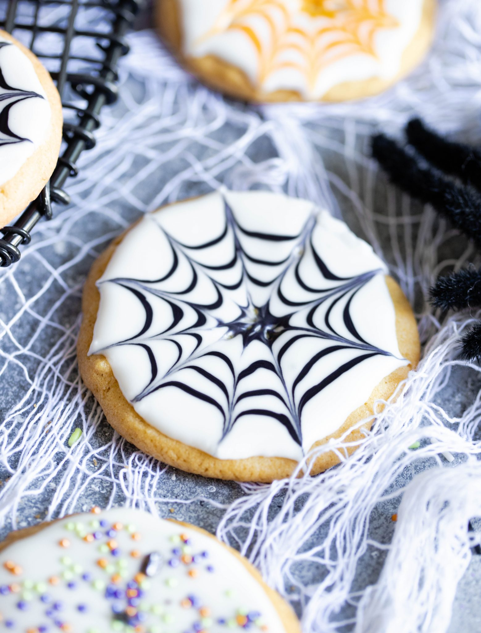 sugar cookie with white icing and a black spider web piped on