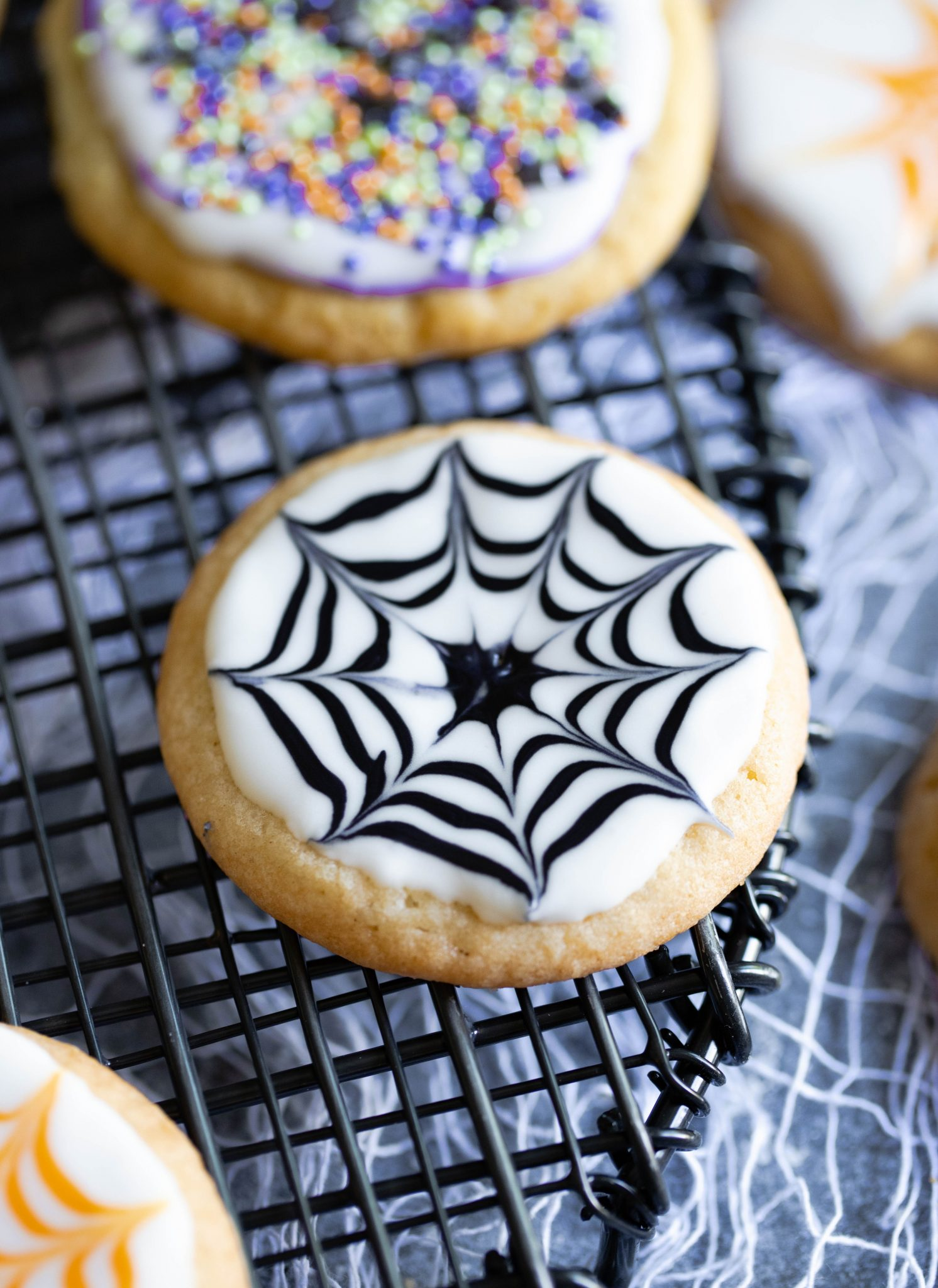 close up shot of halloween cookie with a royal icing spider web decoration