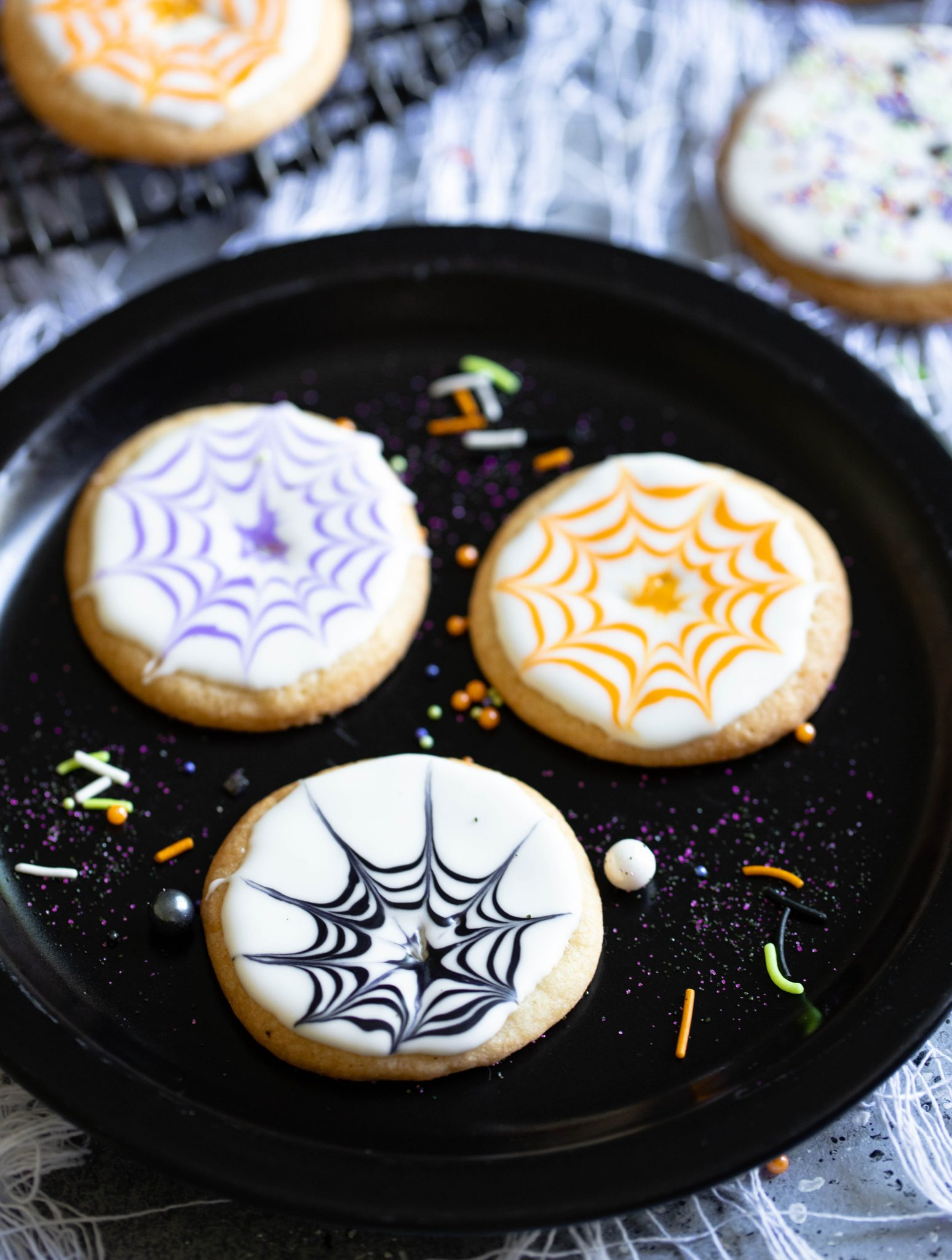 black plate with halloween cookies and sprinkes