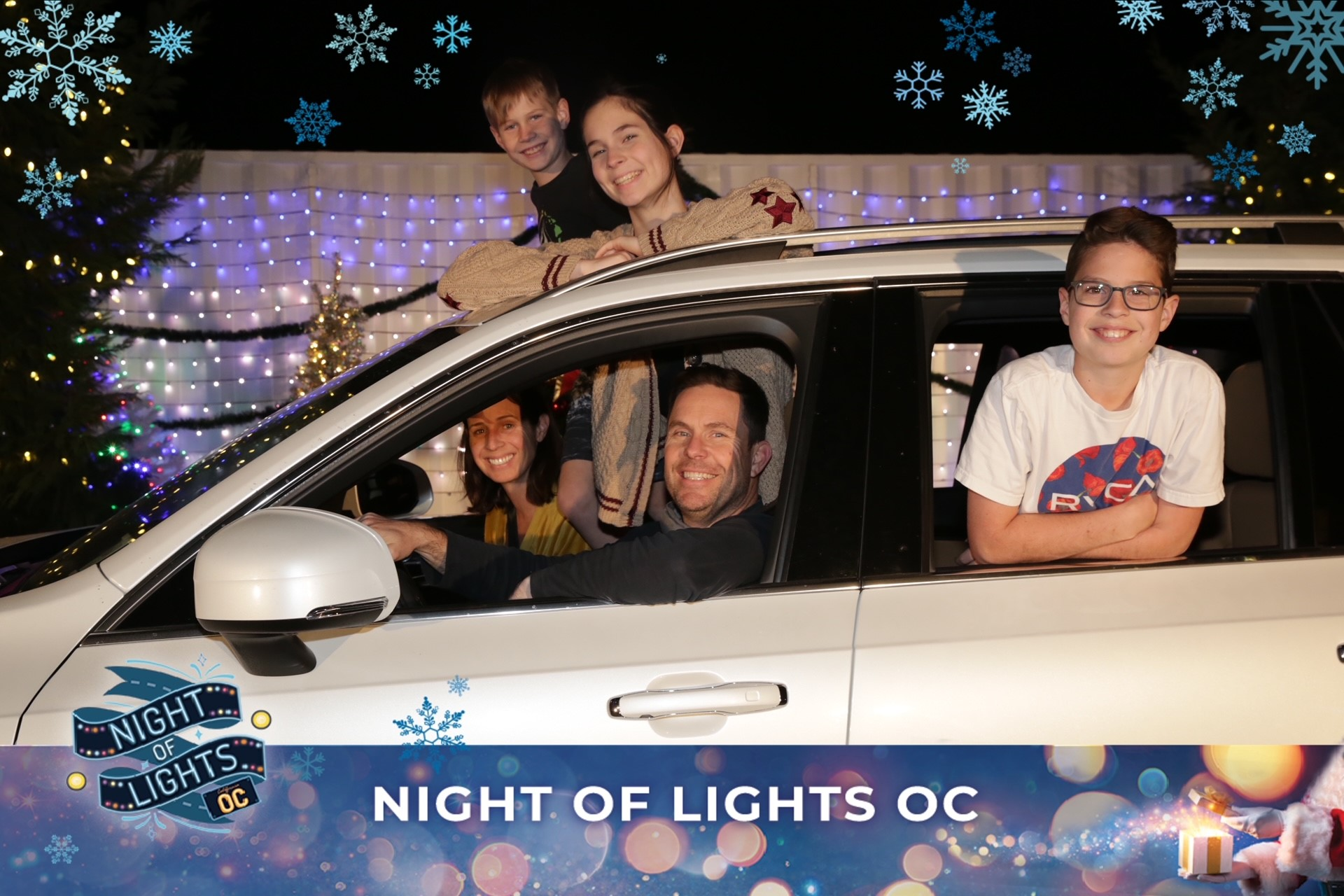 family in car at Night of Lights OC show
