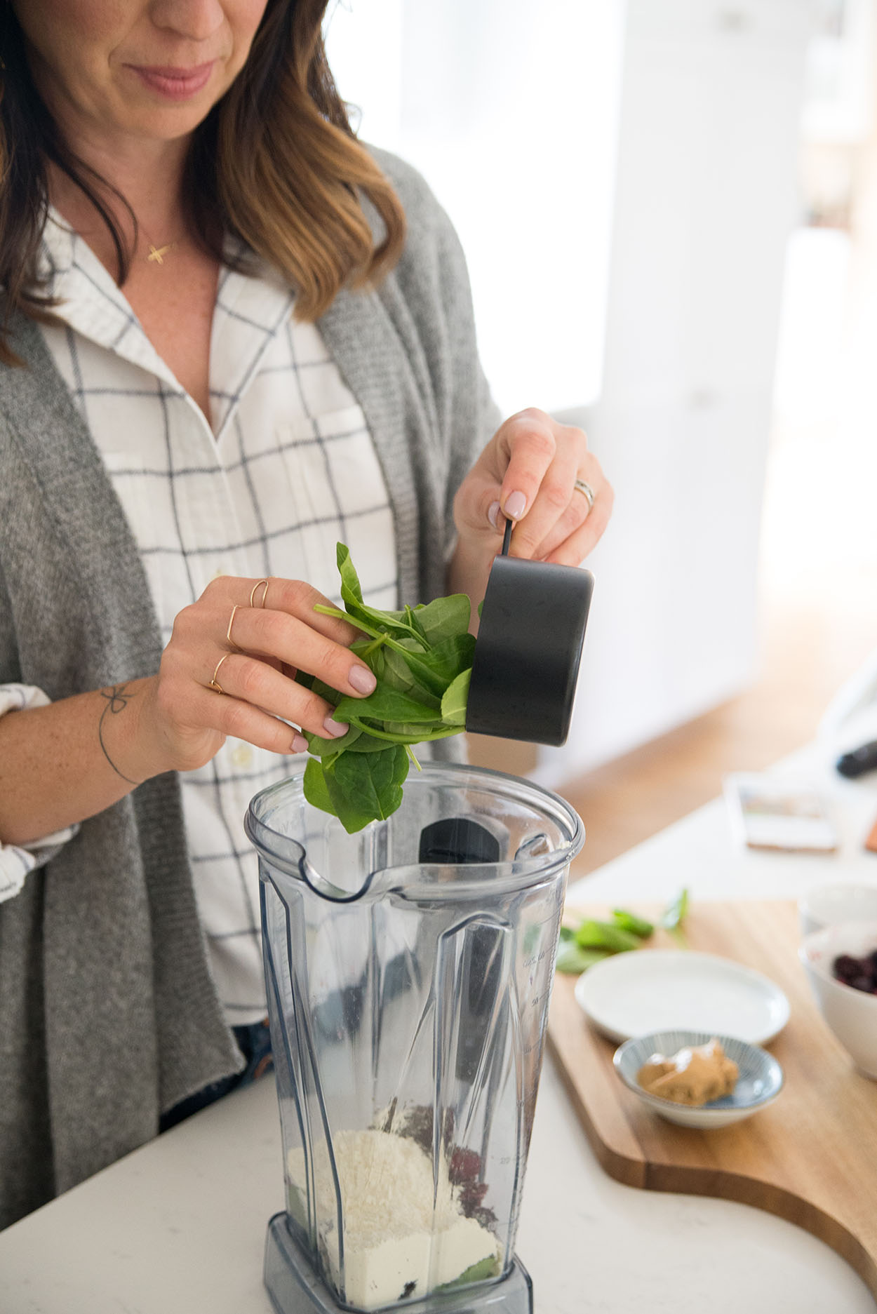 adding spinach to a blender to make a smoothie