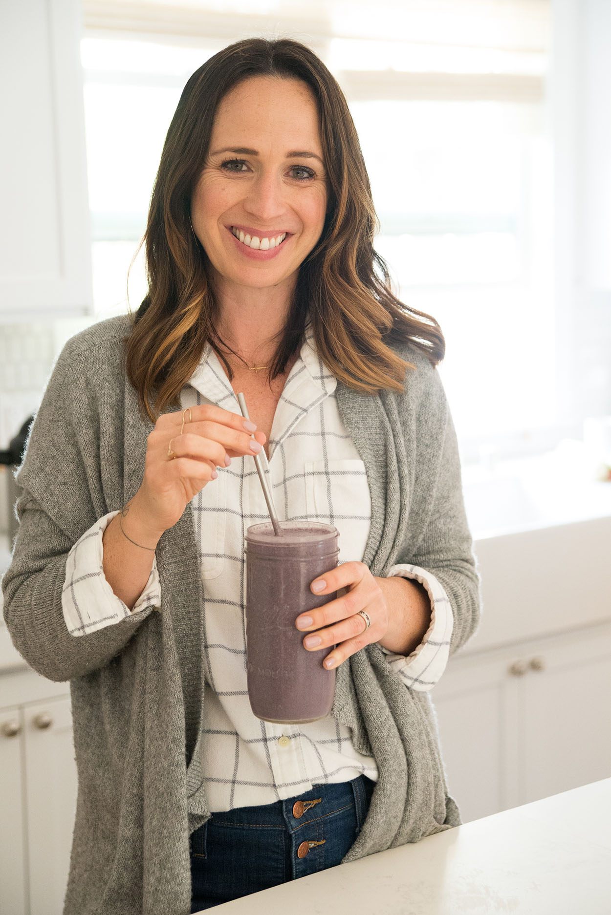 woman smiling holding a berry smoothie