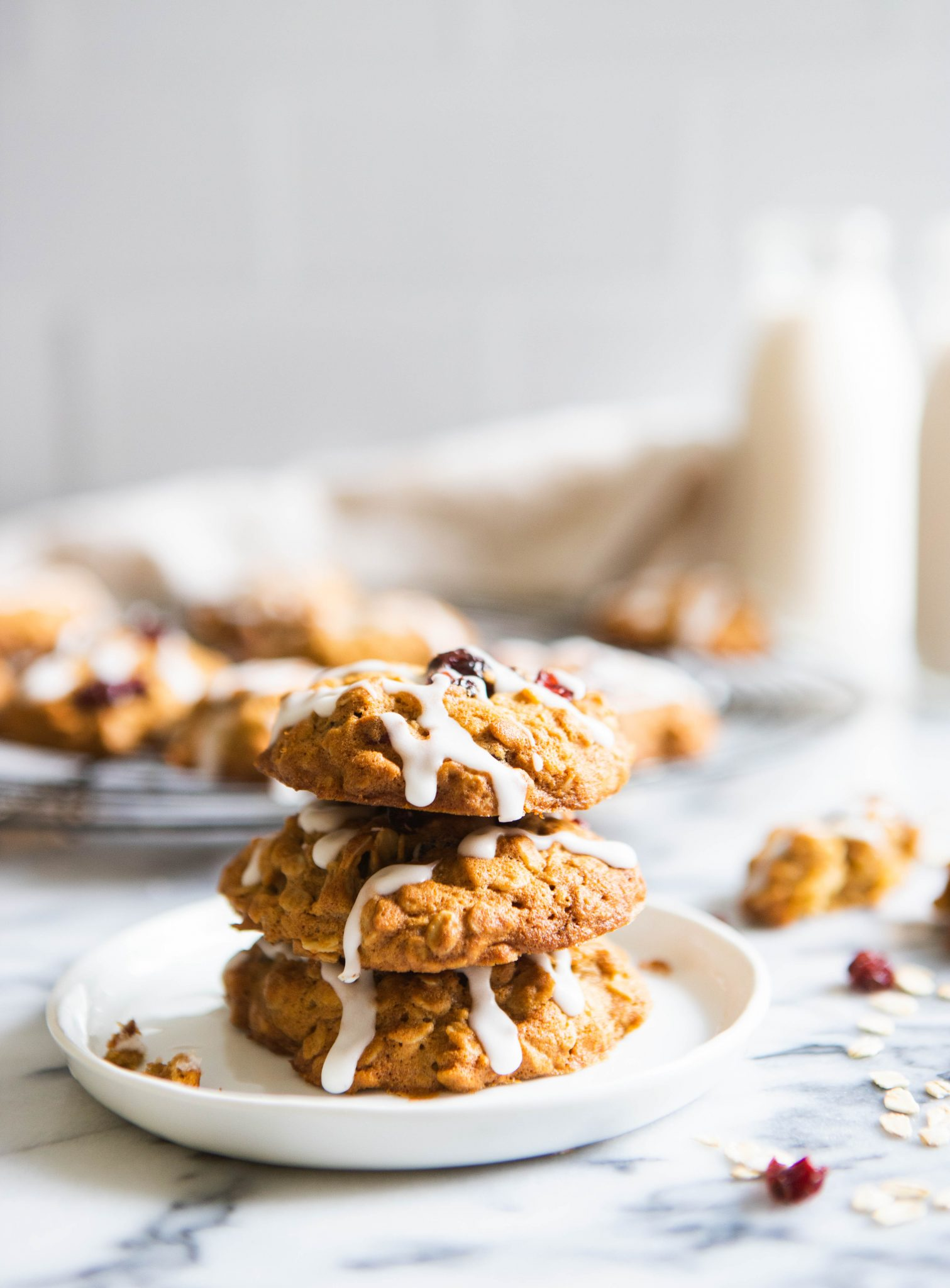 Three oatmeal cookies stacked on a plate with milk in the background