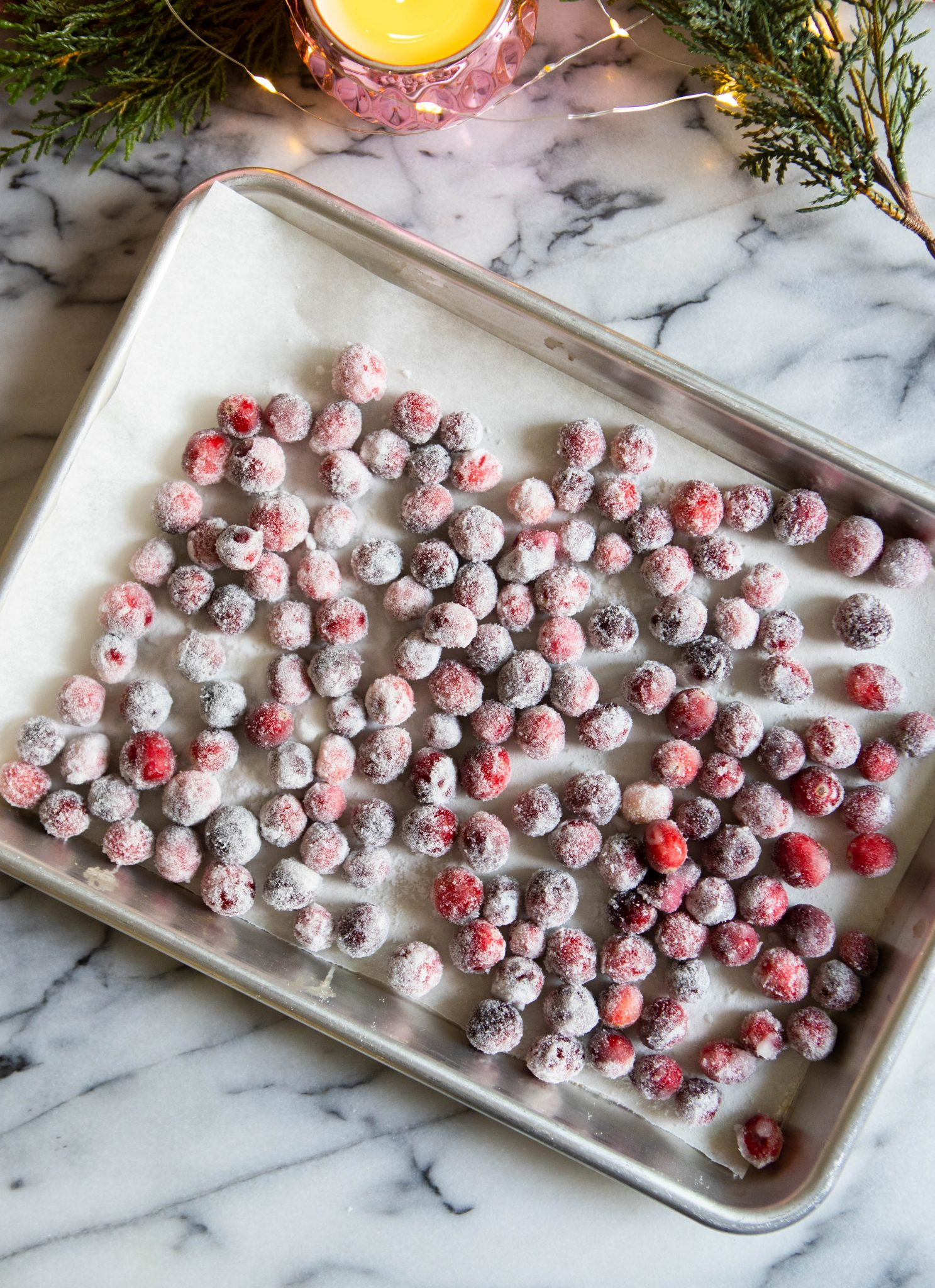 sugared cranberries drying on a baking sheet