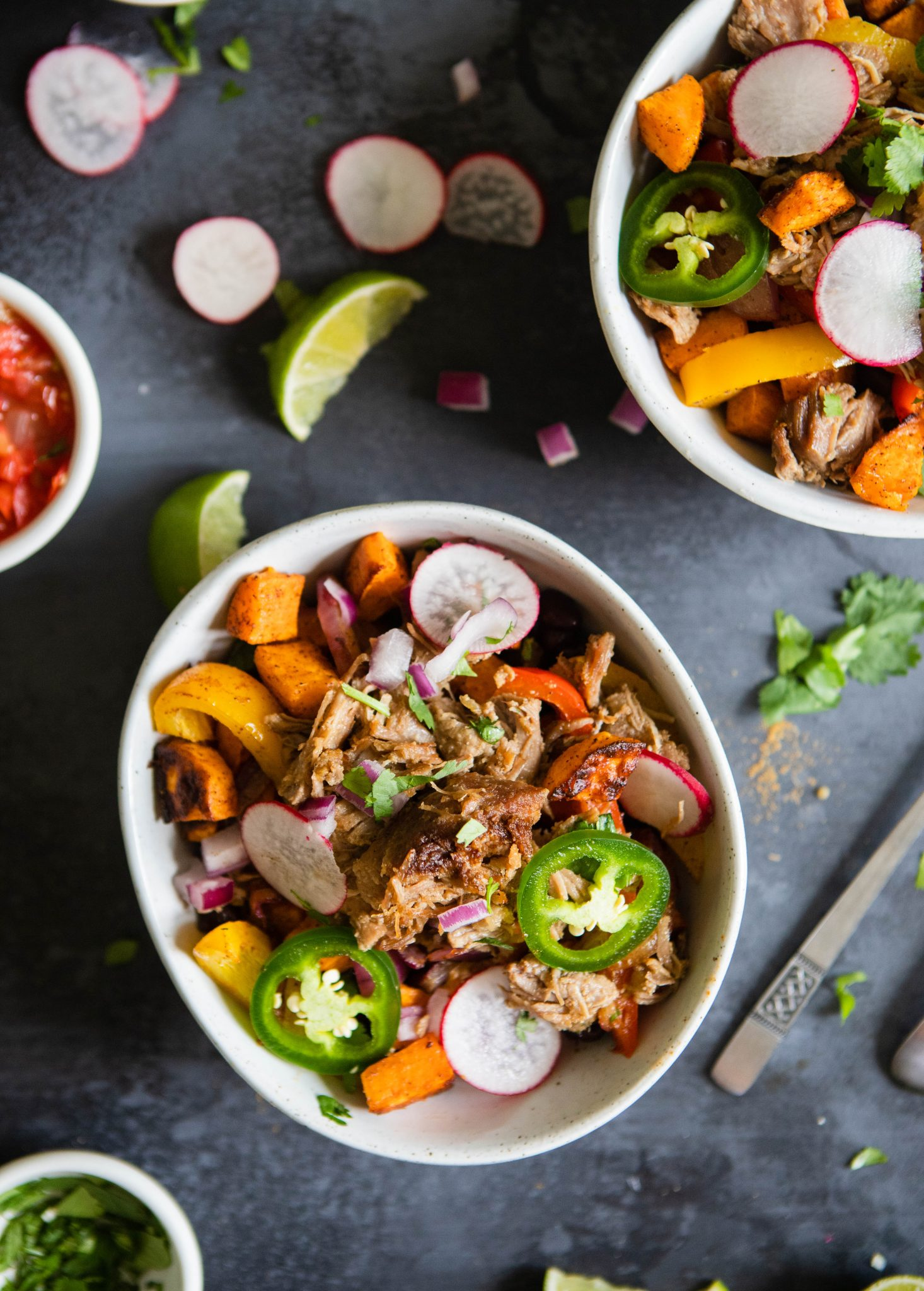 2 bowls filled with carnitas, beans and potatoes and topped with garnishes