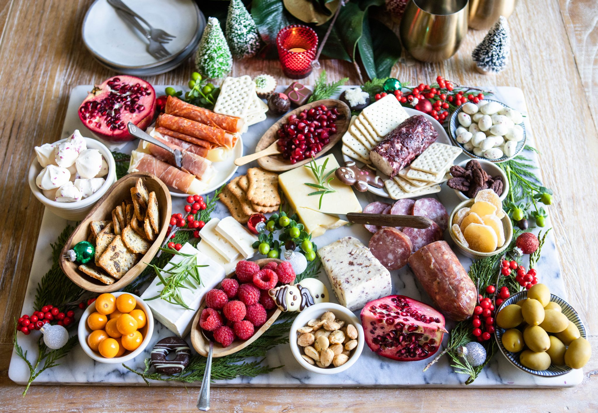 charcuterie board display with meats and cheeses and seasonal greenery
