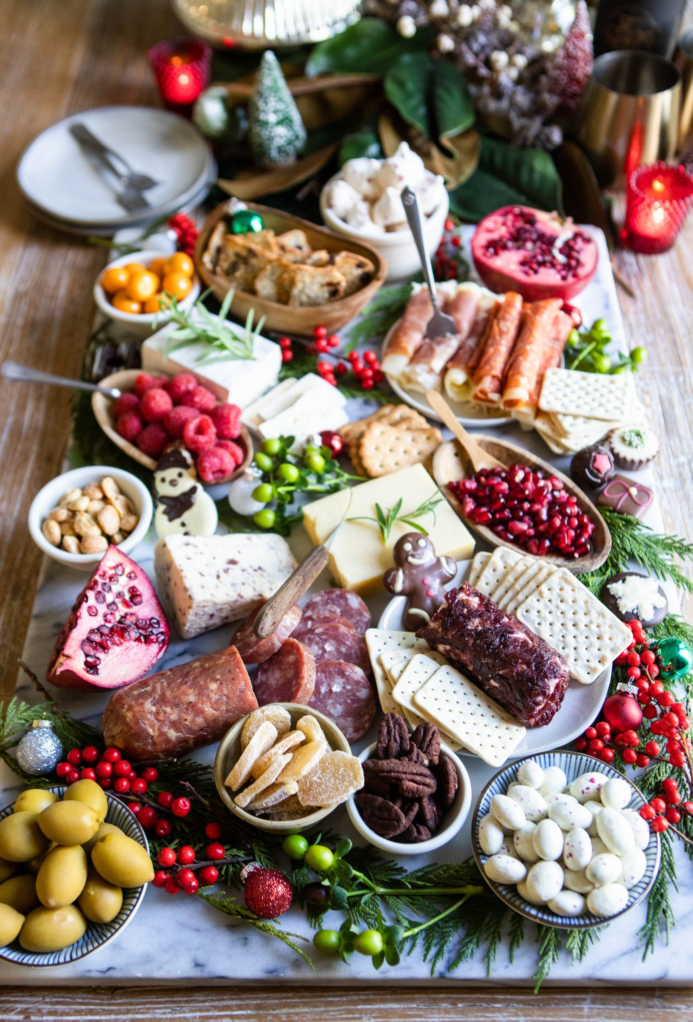cured meats, cheeses, pomegranates and other savory foods on a marble board