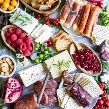 cured meat, blocks of cheese, fruit and nuts on a marble snack board