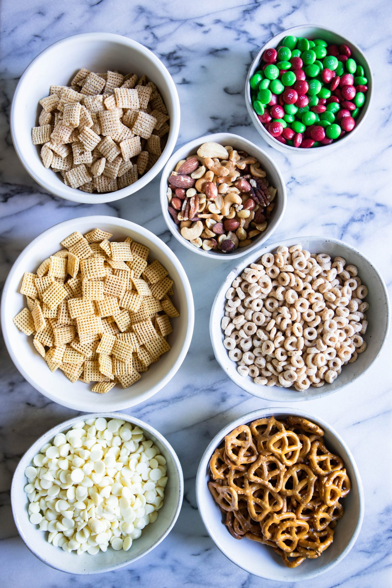white chocolate Chex mix ingredients in white bowls against a marble backdrop