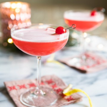Pink cocktail with a foamy egg white top in a coupe glass