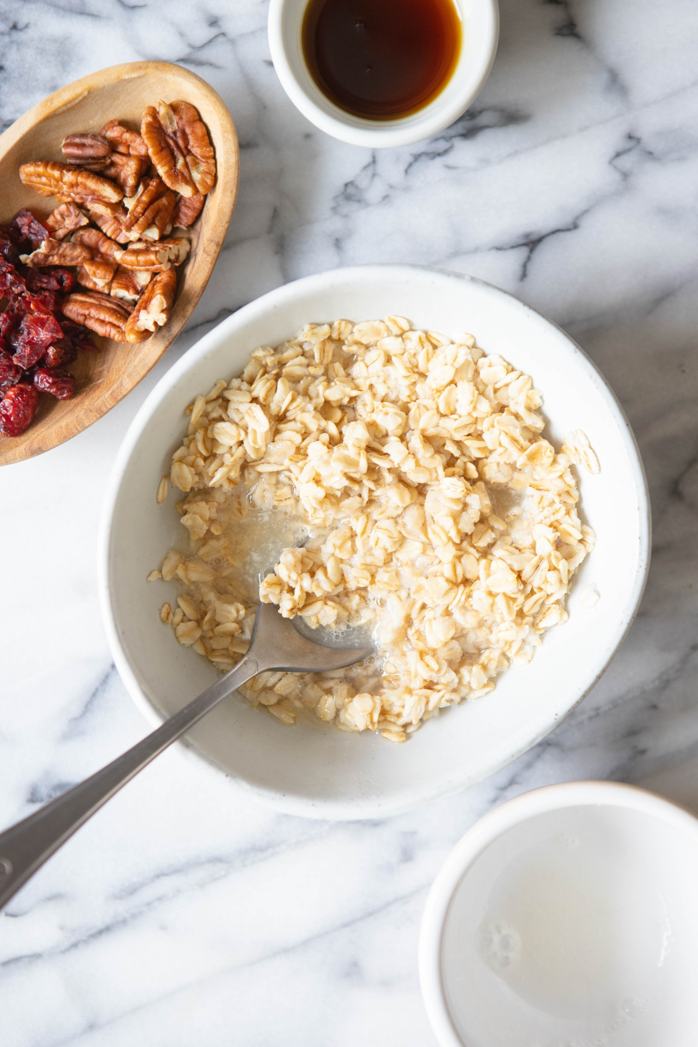 spoon stirring in egg whites into oatmeal in a white bowl