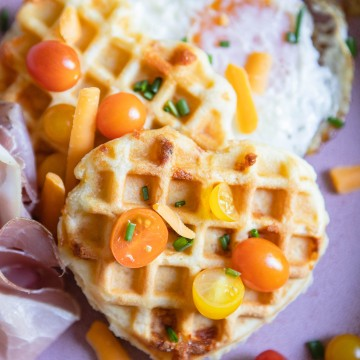 heart shaped waffles topped with tomatoes and chives set on a pink plate