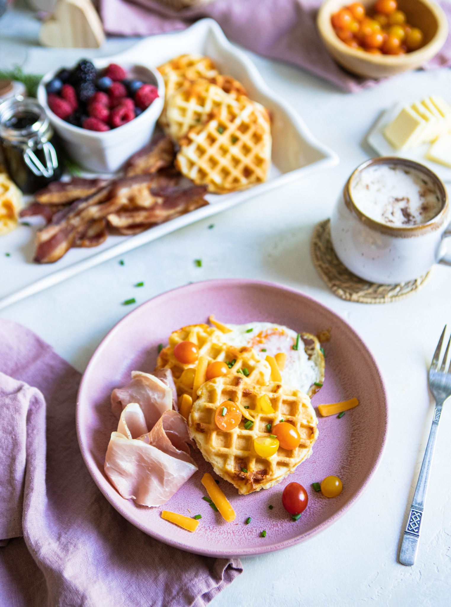 savory waffles on a pink plate next to fruit, and a latte on a white background