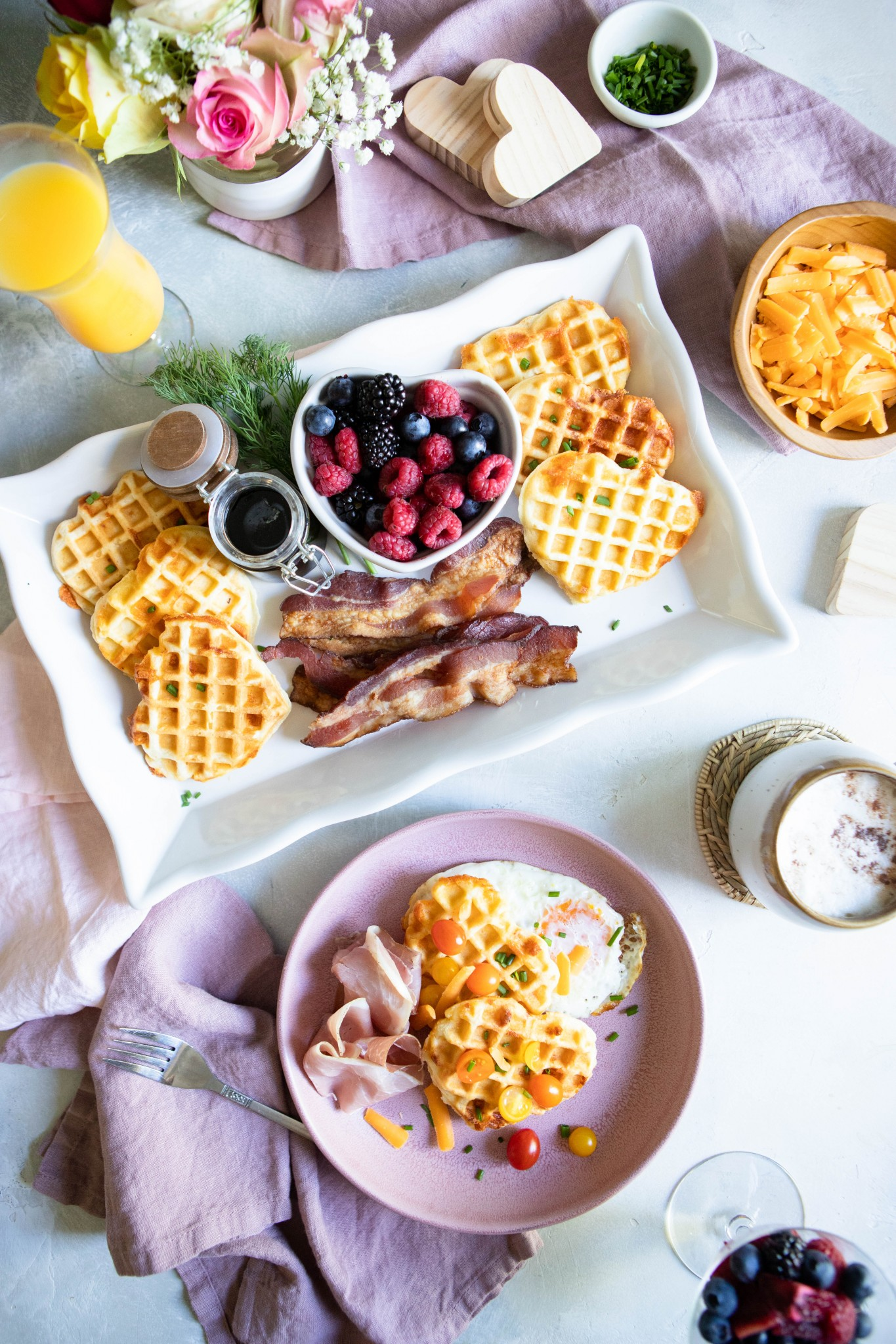 Cheddar and buttermilk waffles on a platter with fruit, bacon and tomatoes