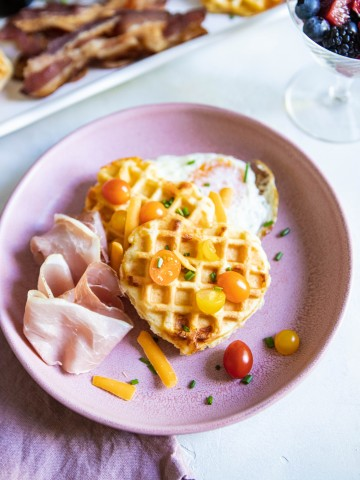 Buttermilk Belgian Waffles on a pink plate topped with tomatoes, cheese and egg