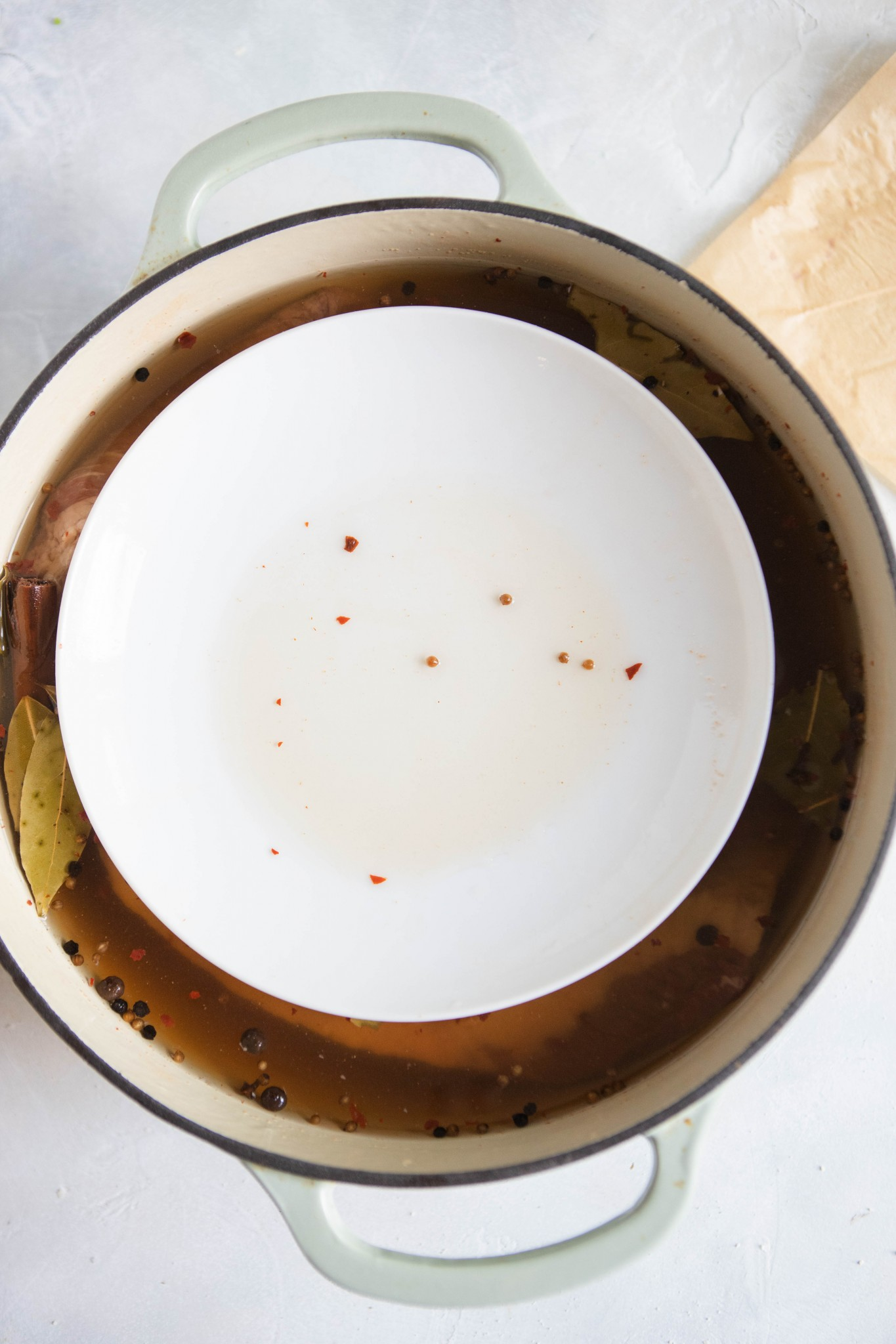 plate set over beef brisket sitting in brine
