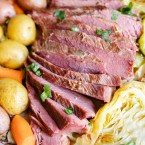 slices of homemade beef brisket nestled in between potatoes, carrots and cabbage