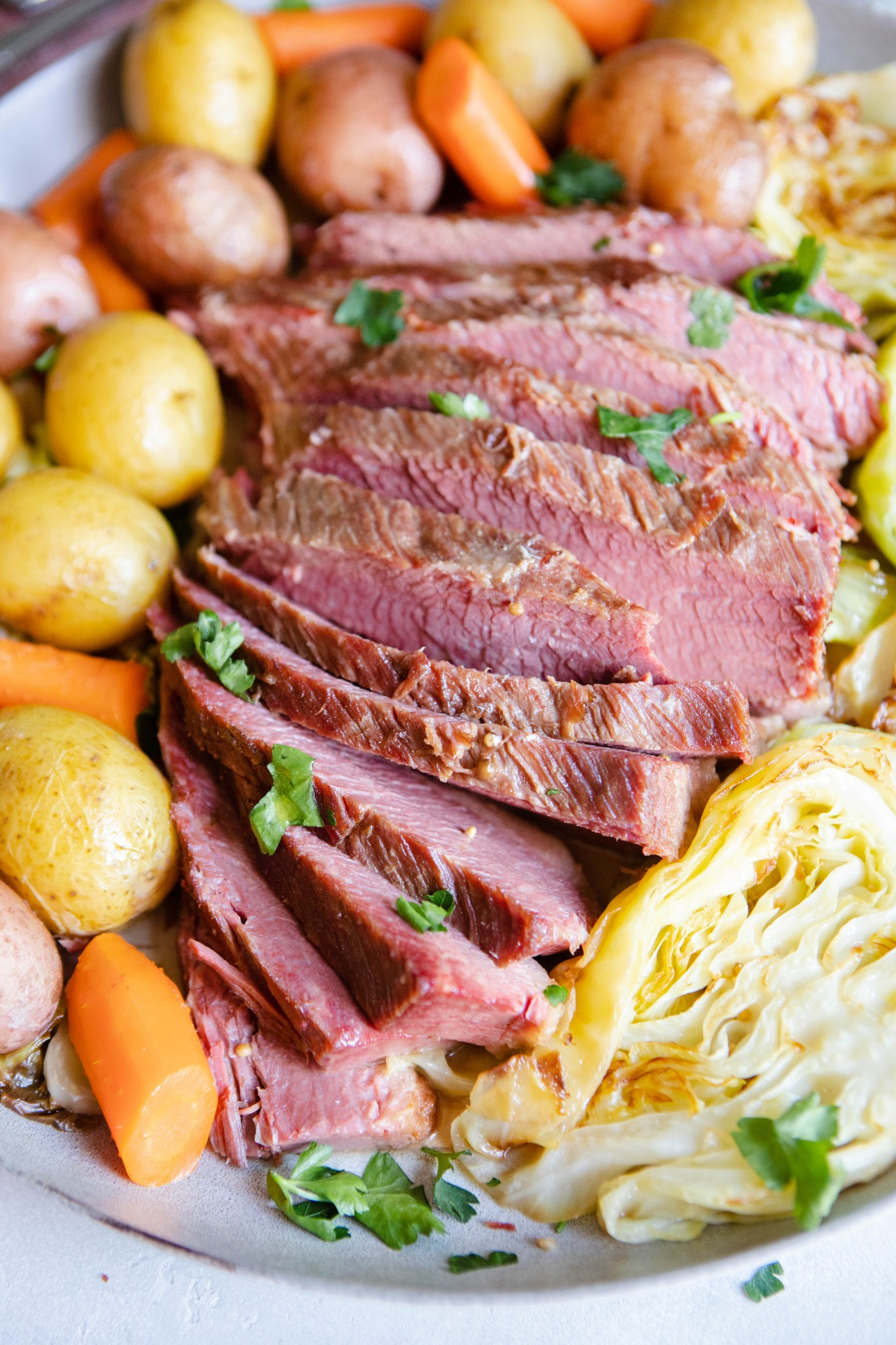 slices of homemade corned beef nestled in between potatoes, carrots and cabbage