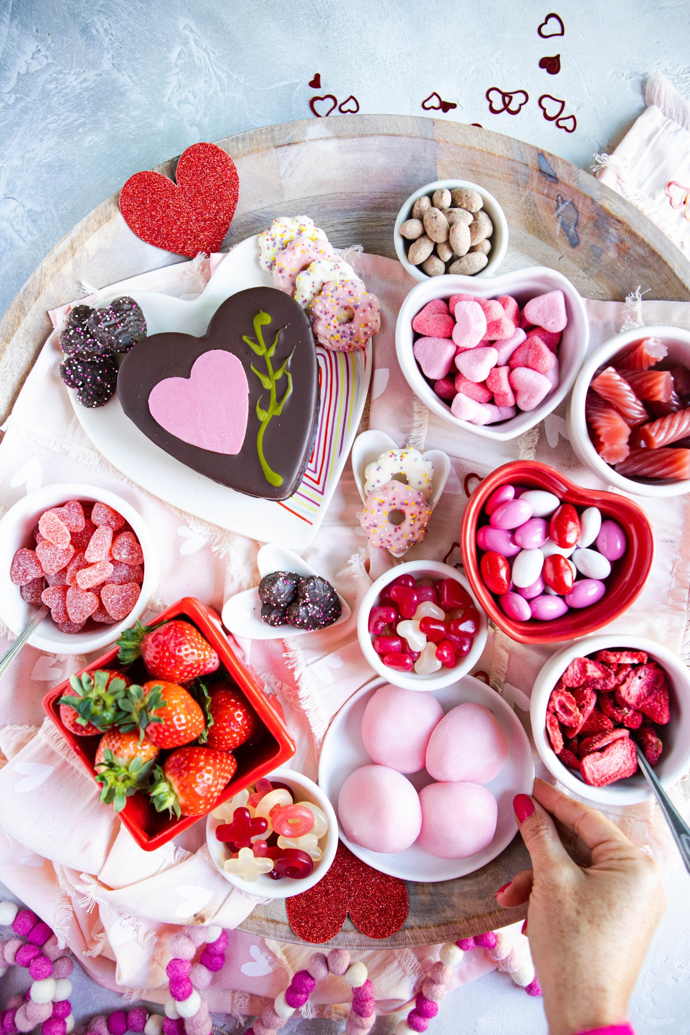 pink mochi ice cream surrounded by other pink and red sweets on a wooden platter