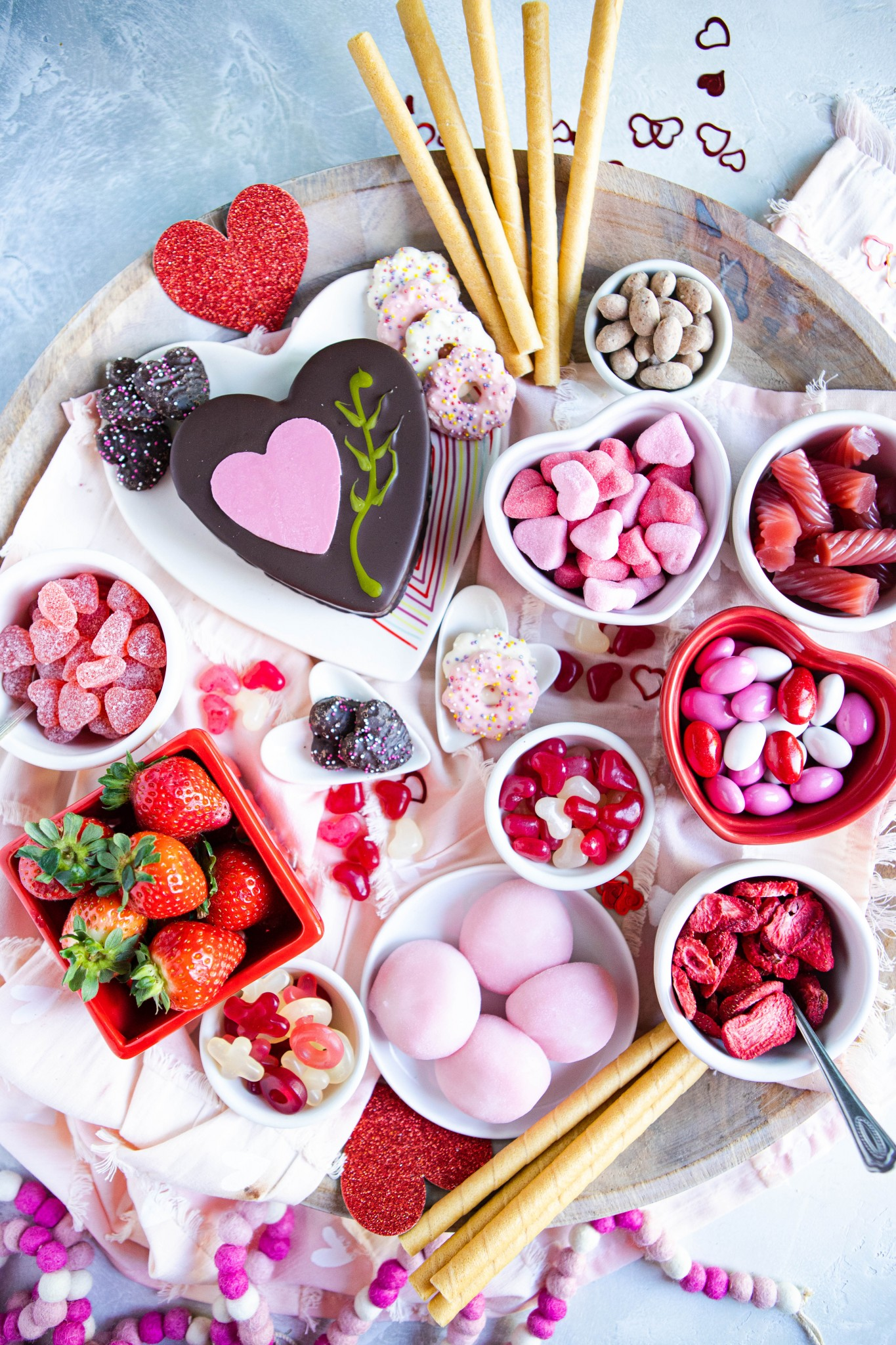 Valentine's dessert charcuterie board filled with pink and red candies, cookies and cakes